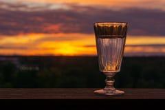 Un vetro di vodka su un fondo di tramonto fotografia stock libera da diritti