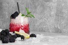 Un vetro enorme del cocktail di frutta rosso con ghiaccio, fette di limone fresco, menta e more su un fondo grigio chiaro Fotografia Stock