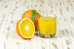 Un vetro intere e mezze delle arance del succo d'arancia, su backgr di legno Fotografia Stock