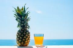Un vetro riempito di succo contro il contesto del mare Frutta fresca dell'ananas Alimento sano fotografie stock libere da diritti