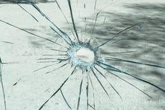 Un vetro rotto con un foro nel mezzo Fotografie Stock