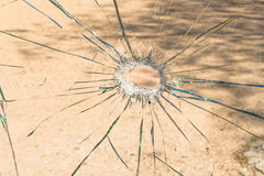 Un vetro rotto con un foro nel mezzo Immagini Stock