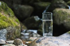 Un vetro/vetro trasparente con l'acqua di fiume minerale della montagna sta su una pietra accanto all'insenatura del fiume della  Fotografia Stock Libera da Diritti