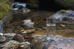 Un vetro/vetro trasparente con l'acqua di fiume minerale della montagna sta su una pietra accanto all'insenatura del fiume della  Immagini Stock Libere da Diritti