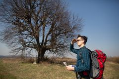 Un viaggiatore con uno zaino, esaminante la mappa e camminante nella campagna Albero nei precedenti immagini stock