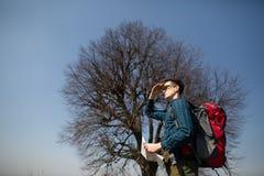 Un viaggiatore con uno zaino, esaminante la mappa e camminante nella campagna Albero nei precedenti fotografie stock libere da diritti