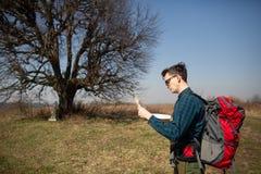 Un viaggiatore con uno zaino, esaminante la mappa e camminante nella campagna Albero nei precedenti immagine stock
