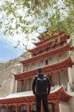 Un viaggiatore con zaino e sacco a pelo a Mogao frana Dunhuang, Cina Fotografia Stock Libera da Diritti