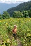 Un viaggiatore del ragazzo con i pali di un trekking cammina lungo una pista in erba alta spessa immagini stock libere da diritti