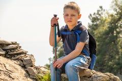 Un viaggiatore del ragazzo con i pali di trekking e uno zaino riposa sopra una montagna fra la foresta verde immagine stock libera da diritti