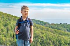 Un viaggiatore del ragazzo con i pali di trekking e uno zaino sta sopra una montagna fra la foresta verde fotografie stock