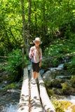 Un viaggiatore del ragazzo con i pali di un trekking sta su un ponte traballante sopra una corrente veloce immagine stock
