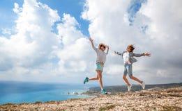 Un viaggiatore di due ragazze che salta contro una bella La sbalorditiva Fotografia Stock Libera da Diritti