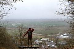 Un viaggiatore esamina il mondo da un'altezza ed i pari nel campo verde, in sua mano il viaggiatore tiene Fotografia Stock