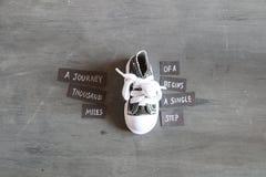 Un viaggio di mille miglia comincia con il singolo punto, la citazione e le scarpe da tennis Immagini Stock