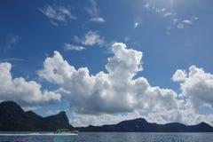 Un viaje del barco con una isla en el fondo Imágenes de archivo libres de regalías