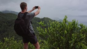 Un viajero con una mochila en el suyo detrás, los soportes en el top de una colina y tira un paisaje en su teléfono móvil almacen de metraje de vídeo