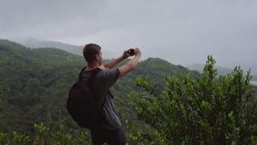 Un viajero con una mochila en el suyo detr?s, los soportes en el top de una colina y tira un paisaje en su tel?fono m?vil almacen de video