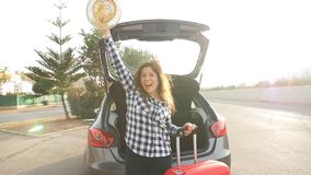 Un viajero de la mujer joven con una maleta se coloca cerca de su coche metrajes