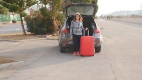 Un viajero de la mujer joven con una maleta se coloca cerca de su coche almacen de video