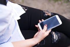 Un viajero de la mujer joven se sienta al lado de las mochilas y de escuchar la música por smartphone Imágenes de archivo libres de regalías
