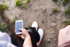 Un viajero de la mujer joven se sienta al lado de las mochilas y de escuchar la música por smartphone Fotografía de archivo libre de regalías