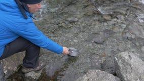 Un viajero del hombre dibuja el agua en un río de la montaña para cocinar la comida en un alza metrajes