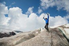 Un viajero en un casquillo y gafas de sol con brazos y hachas de hielo aumentados significando la victoria en las montañas nevosa imagenes de archivo
