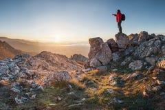 Un viajero feliz en un top de la montaña Fotografía de archivo libre de regalías