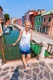 Un viajero femenino se coloca en un puente a través de un canal en la isla de Burano con muchas casas coloridas en el fondo Fotografía de archivo