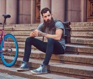 Un viajero hermoso del inconformista con una barba elegante y el tatuaje en sus brazos se vistieron en la ropa casual, sentándose imagen de archivo libre de regalías