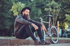 Un viajero hermoso del inconformista con una barba elegante y el tatuaje en sus brazos se vistieron en ropa casual y sombrero con foto de archivo