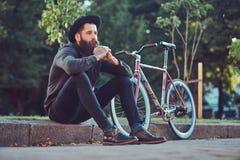Un viajero hermoso del inconformista con una barba elegante y el tatuaje en sus brazos se vistieron en ropa casual y sombrero con fotografía de archivo