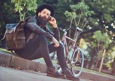 Un viajero hermoso del inconformista con una barba elegante y el tatuaje en sus brazos se vistieron en ropa casual y sombrero con imagen de archivo libre de regalías