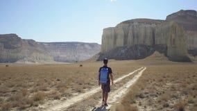 Un viajero joven camina a lo largo de una trayectoria en un área montañosa metrajes