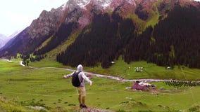 Un viajero joven con una mochila se coloca al borde de la garganta de las montañas y de las miradas alrededor almacen de video