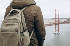 Un viajero joven o un turista con una mochila en la costa en Lisboa en Portugal al lado del 25to de April Bridge Imágenes de archivo libres de regalías