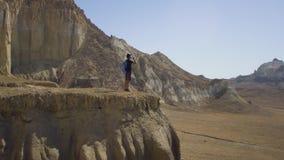Un viajero joven se coloca al borde de un acantilado y de un agua de las bebidas metrajes