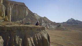 Un viajero joven se sienta al borde de un acantilado y de un agua de las bebidas almacen de video