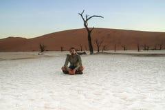 Un viajero masculino caucásico blanco joven en la ropa de deportes que se sienta en una tierra blanca seca en el parque nacional  imagen de archivo