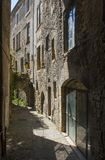 Un vicolo stretto tipico nella città di Montelimar in Francia con le costruzioni, le entrate e le ombre scure di pietra alte Fotografie Stock