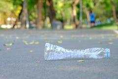 Un vide de la bouteille potable en plastique salissant sur le plancher de route au parc vert avec le fond de nature de vert de ta image stock