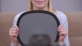 Un video blogger femminile prima della fucilazione del vlog mette l'equilibrio bianco nella macchina fotografica facendo uso di u archivi video