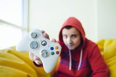 Un videojugador joven muestra un cierre blanco de la palanca de mando del juego del videojugador para arriba Videojuegos del conc Imágenes de archivo libres de regalías