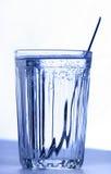 Un vidrio con agua y la cucharilla imagen de archivo