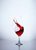 Un vidrio con el vino rojo y los esprayes Imagen de archivo libre de regalías