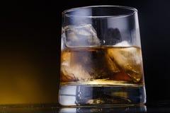 Un vidrio con el whisky y el hielo en un fondo fotografía de archivo libre de regalías