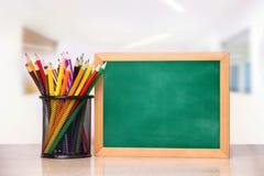 Un vidrio con los lápices y un consejo escolar para escribir en una tabla de madera Imagen de archivo libre de regalías