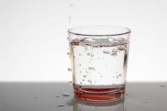 Un vidrio de agua con las burbujas y salpica Imagenes de archivo