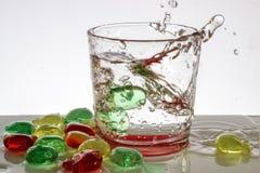 Un vidrio de agua con las burbujas y salpica Foto de archivo